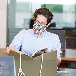 researcher in colorful mask looking at document in Rose Library