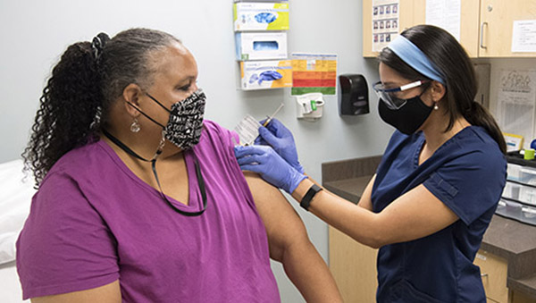woman in magenta top and mask getting a shot from nurse