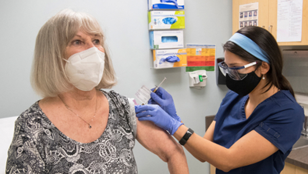 older woman in black and white top and mask getting a shot from nurse