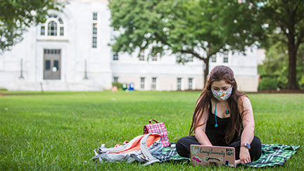 masked student using a laptop while sitting on the quad
